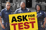 Police Officers hold sign reading 'Ask for the test'