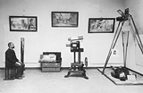 Historical photograph of a man sitting in a room with multiple mirrors and a complex camera equipment set-up