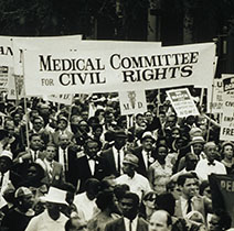 A large crowd of people, some who are holding signs. The largest sign with black lettering on a white background states: Medical Committee for Civil Rights.