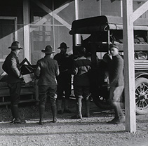 Four soliders load a patient in a stretcher on the back on a truck.
