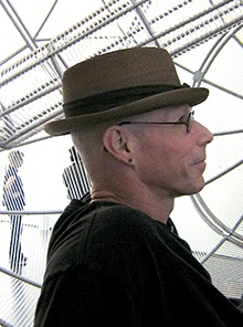 Half-length photograph of Michael Sappol wearing glasses looking downat papers he is holding with his left hand and a pen in his right.