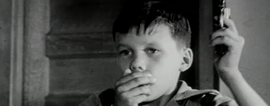 A young boy covering his mouth with his right hand.