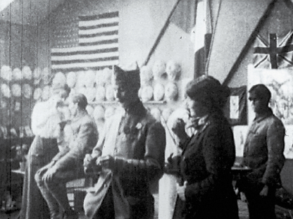 Artists and men in uniform in a studio with plaster masks hung on the wall.