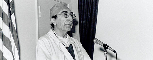 Michael DeBakey standing at a podium in scrubs.