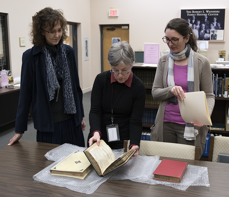 Three women examine books on a table.