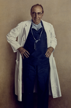 Michael DeBakey standing in blue scrubs and a white lab coat with his hands on his hips.