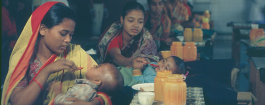 A group of women feeding infants.