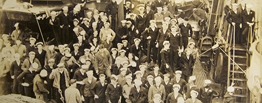 A crowd of sailors on a military vessel.