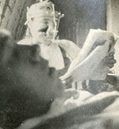 A wounded soldier reads at another's bedside.