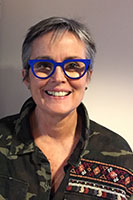 A white woman with grey hair and blue glasses.