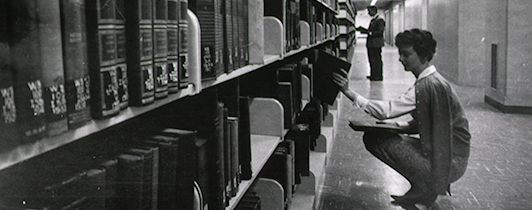 A woman kneels down to remove a book from the library stacks.