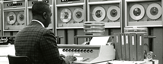 A man works at a keyboard surrounded by large tape data storage machines.