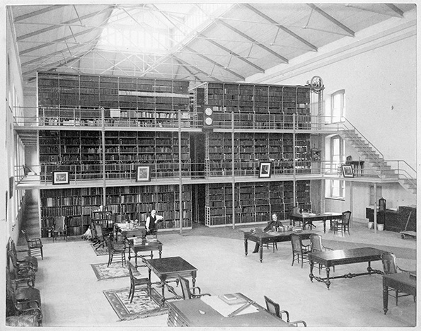 A photograph of men in uniform reading in a library.