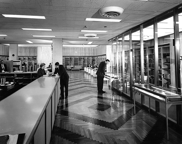 Photograph of a library entrance with people standing around different areas.