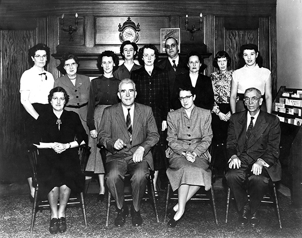 Photograph of a group of people sitting and standing.