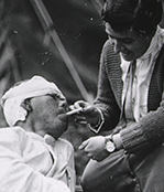 A woman lights a cigarette for a wounded man.