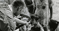 A man examines a child's mouth outdoors.
