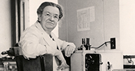 Florence Sabin at a desk with a microscope