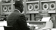 A man types in computer commands to be performed and processed by magnetic tape in the OCCS computer room.