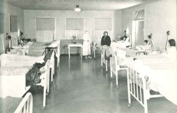 Black and white photograph of several patients lying in their beds inside of a hospital ward.