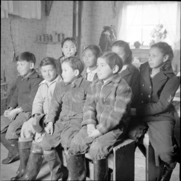Black and white photograph of eight Unangan children sitting on two benches.