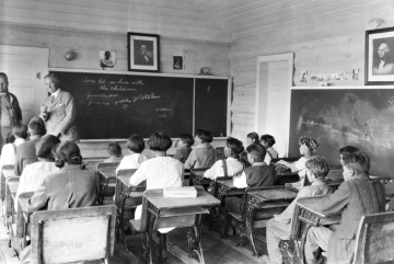 Black and white photograph of several Native American children at their desks inside of a one-room schoolhouse.