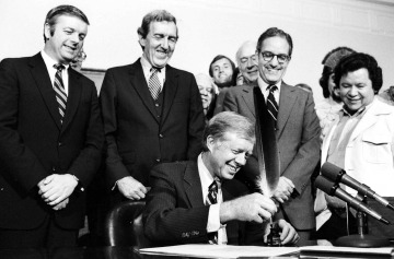 President Jimmy Carter uses an Indian quill pen to sign the Maine Indian Claims Settlement Act