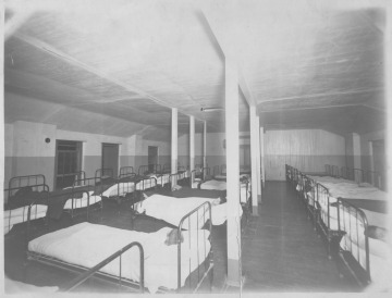 Black and white photograph depicting a large room with several rows of identical beds occupied by Native American boys.